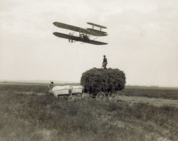 Wilbur Wright instructing a student pilot in Pau, France, passes over an ox cart in 1909