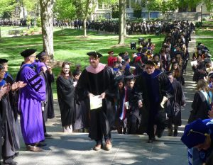 Faculty marshals begin leading the graduates through the lines of faculty and through Kauke Arch