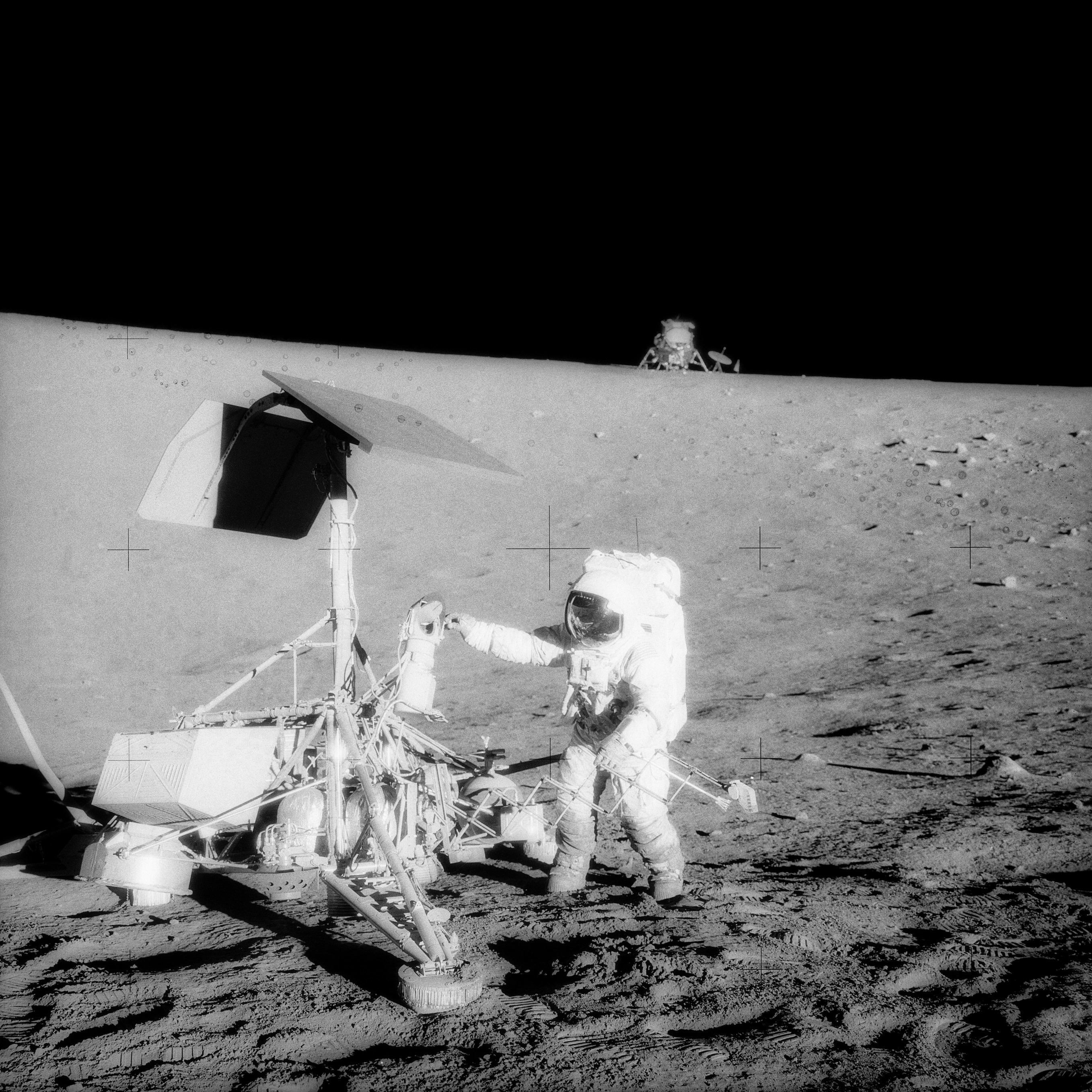 Al Bean photographed Pete Conrad at the Surveyor 3 spacecraft with the lunar module Intrepid on the horizon, November 20, 1969
