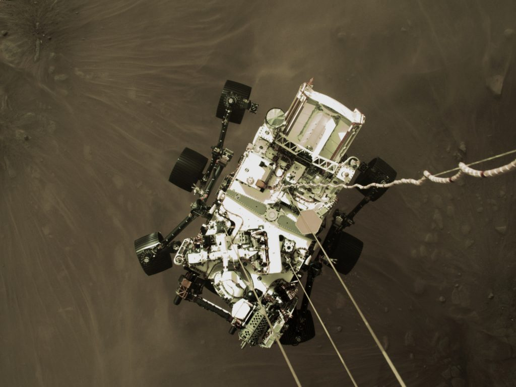 The car-sized Perseverance rover, suspended by tethers from its powered descent stage, a couple of meters above the surface, just seconds before touchdown, on Mars